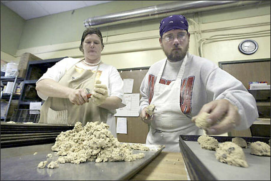 Lisa Van Benschoten, left, and Bartt Reynold scoop up raisin oatmeal dough at Cookie Creations, a profit-sharing cooperative run by mentally ill workers. (Note: Reynold's name was mispelled originally.) Photo: Jim Bryant/Seattle Post-Intelligencer
