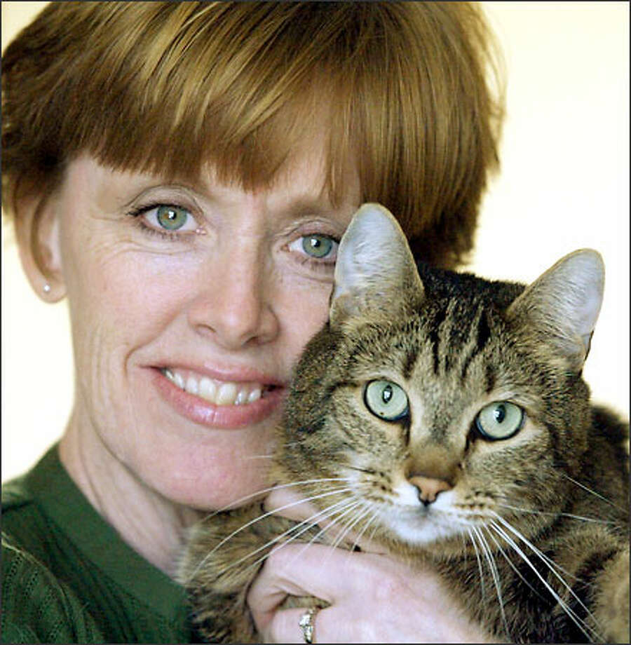 """For a cat who started out """"so homely and ugly that no one would adopt him,"""" life is sweet for Bengal (with owner Dee Cordell). Photo: Phil H. Webber/Seattle Post-Intelligencer"""