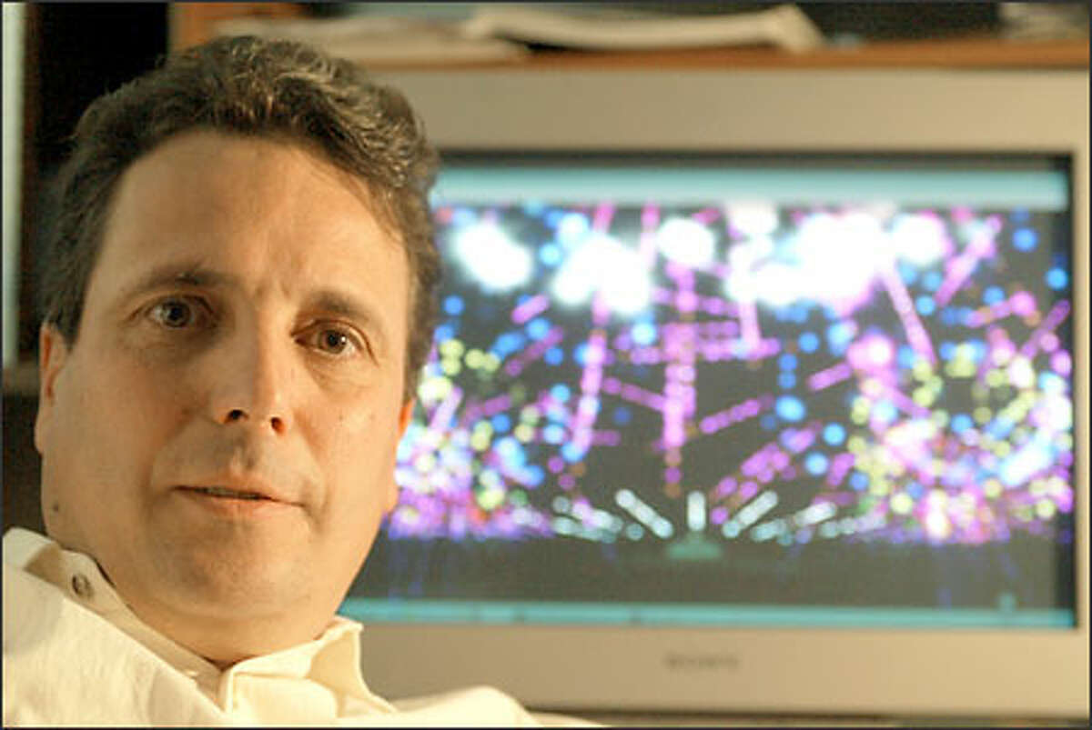 """Alberto Navarro, 46-year-old founder of Infinity Visions, with one of his fireworks programs in the background. Navarro says the Space Needle is his favorite place to design a show. """"The structure is unique and it is a threedimensional show. It becomes a sculpture of fire,"""" the """"sky artist"""" says."""