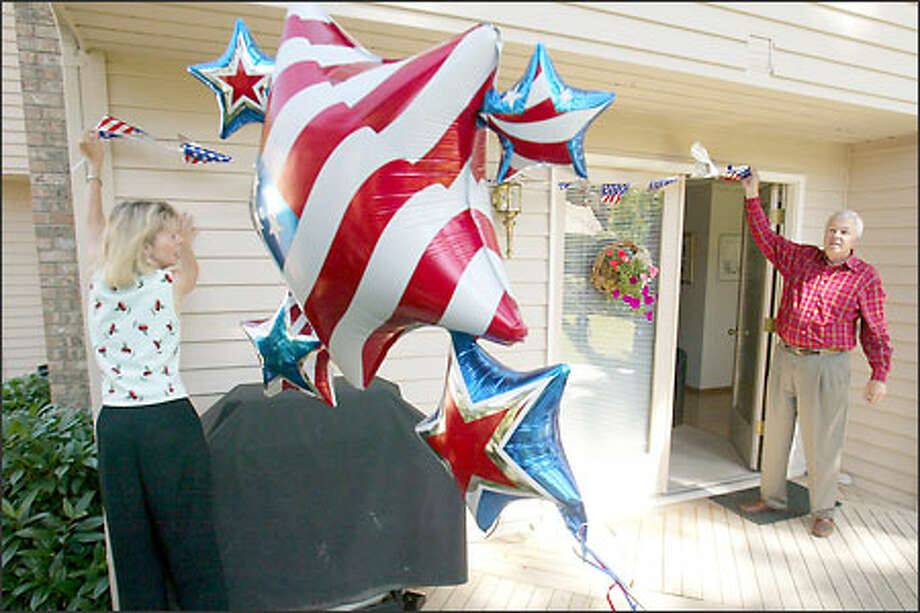 Canadian Dennis Firth, who will become an American citizen at today's Seattle Center ceremony, helps his wife, Lenita, decorate their Mill Creek home. Photo: Mike Urban/Seattle Post-Intelligencer
