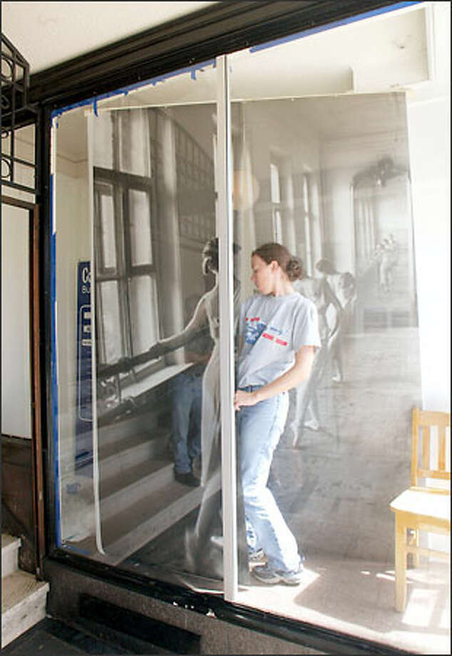 UW achitectural graduate student Joy Shaw slips between two posters she is hanging in the windows of The Ballet Studio on University Way Northeast. Shaw is part of a project rebuilding and revitalizing facades on the Ave. Photo: Mike Urban/Seattle Post-Intelligencer