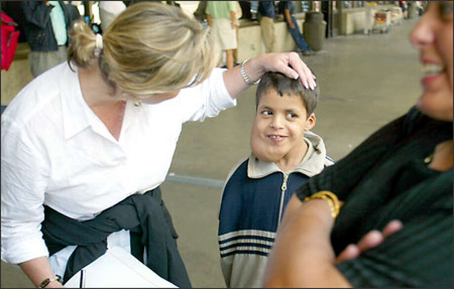 Margaret Larson of Mercy Corps reaches over to pat Ali Mousa on the head as they wait for a ride from Sea-Tac Airport yesterday. Ali, 8, has an inborn tumor in his lymphatic system that affects his breathing and swallowing. Larson, a former KING/5 broadcaster, helped arranged medical care for Ali. Photo: Grant M. Haller/Seattle Post-Intelligencer