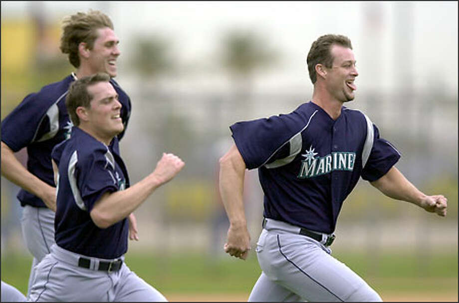 Aaron Taylor, right, running sprints during spring training with pitchers Ryan Anderson, left, and Jeff Heaverlo, has pitched well in two appearances with the Mariners, touching 98 mph with his fastball. Photo: ELAINE THOMPSON/AP