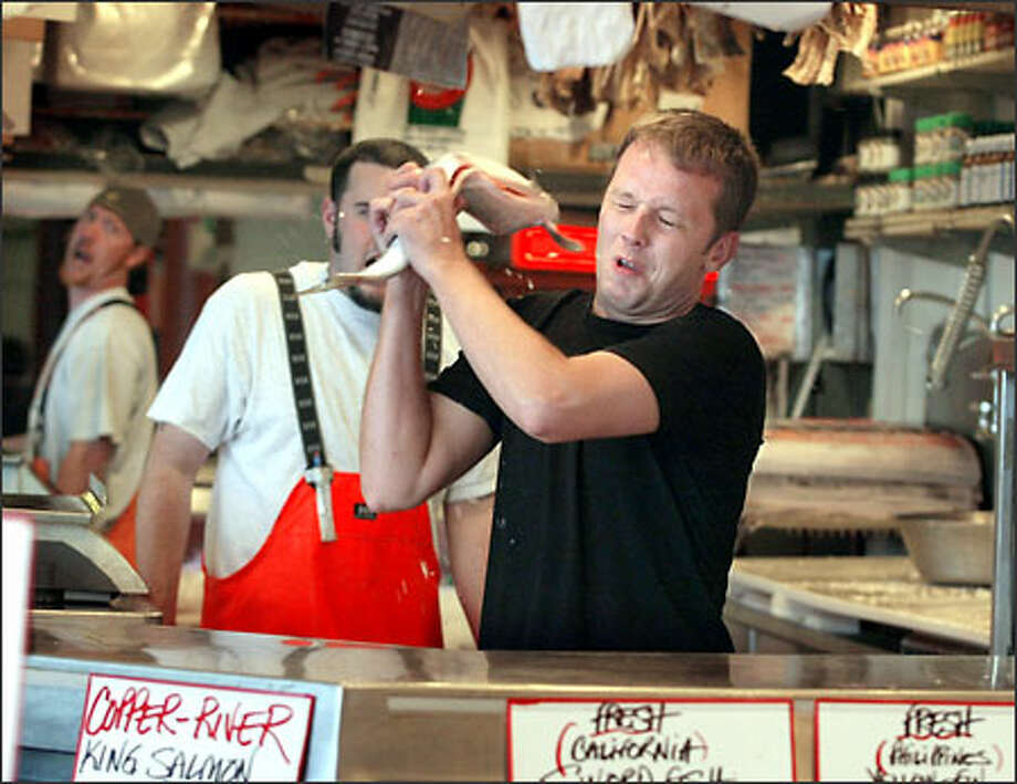 """Andreas Viestad, author of the cookbook """"Kitchen of Light,"""" catches a salmon at Pike Place Market on a visit to Seattle. Photo: Scott Eklund/Seattle Post-Intelligencer"""