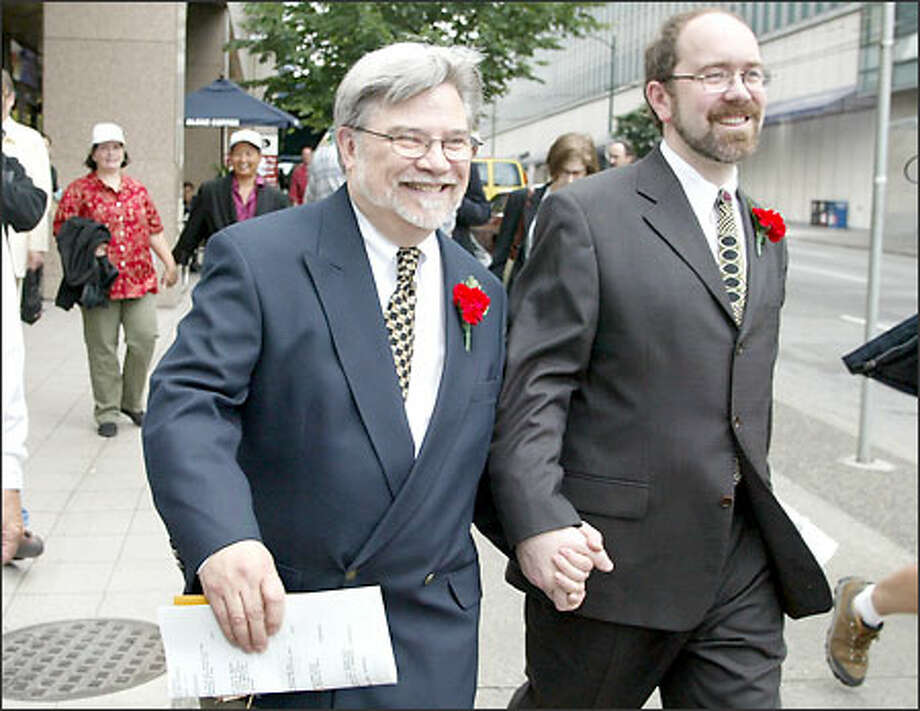 Tom Graff, left, and Antony Porcino head off to get married after obtaining their marriage license at the vital statistics office in Vancouver. Photo: / Associated Press