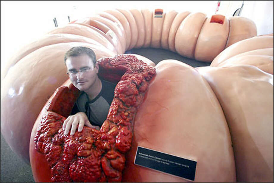 Brandon Nichols, director of Creative Services Event Strategies, Inc., pokes his head out of the huge colon model that promotes awareness of colon cancer. Photo: Jim Bryant/Seattle Post-Intelligencer