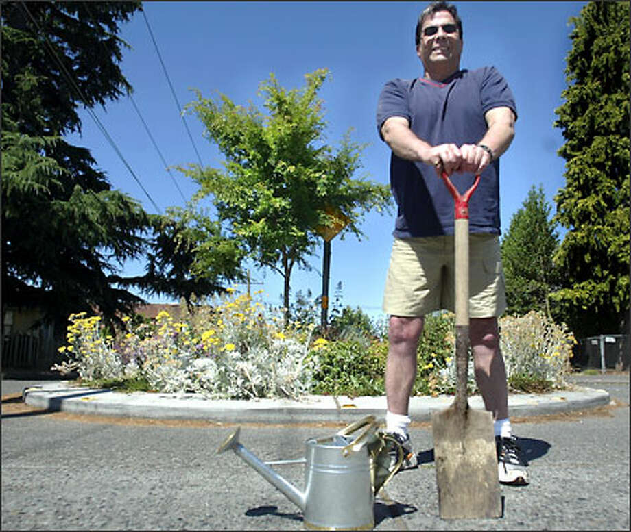 "Ted Kitos got tired of looking at the overgrown traffic circle in his neighborhood in West Seattle two years ago. Since then he has planted a garden of perennials and won the 2002 Streetside Garden Contest in the ""Just for Fun"" category. Photo: Karen Ducey/Seattle Post-Intelligencer"