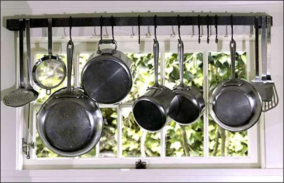 Pots, pans and cooking utensils hang in a window of the 1923 bungalow owned by Jack and Rosemary Boyd. Photo: Jim Bryant/Seattle Post-Intelligencer
