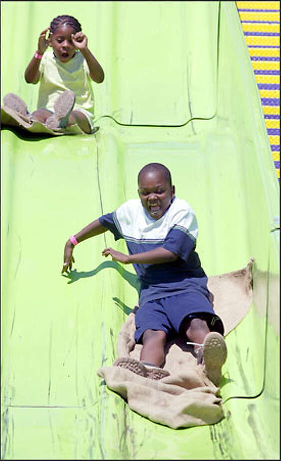 Eight-year-olds Robyn Knott, left, and Jonathan Foster-Knott enjoy a ride on The Super Slide yesterday at Soul Fest. The festival is in its 16th year and continues this weekend at Franklin High School. Photo: David Bitton/Seattle Post-Intelligencer