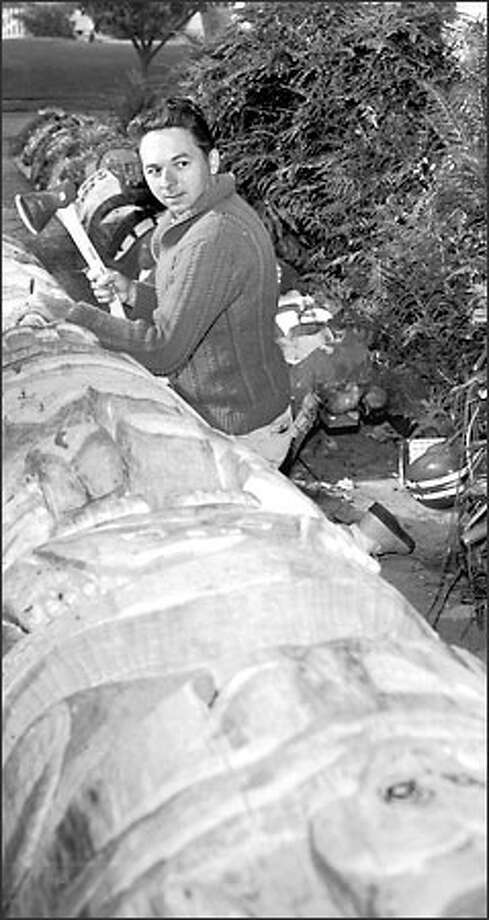 Mike Morgan carving the 24-foot totem pole that has been staring toward Seattle's downtown skyline since 1966, a fixture in Belvedere Viewpoint Park in West Seattle. Photo: /