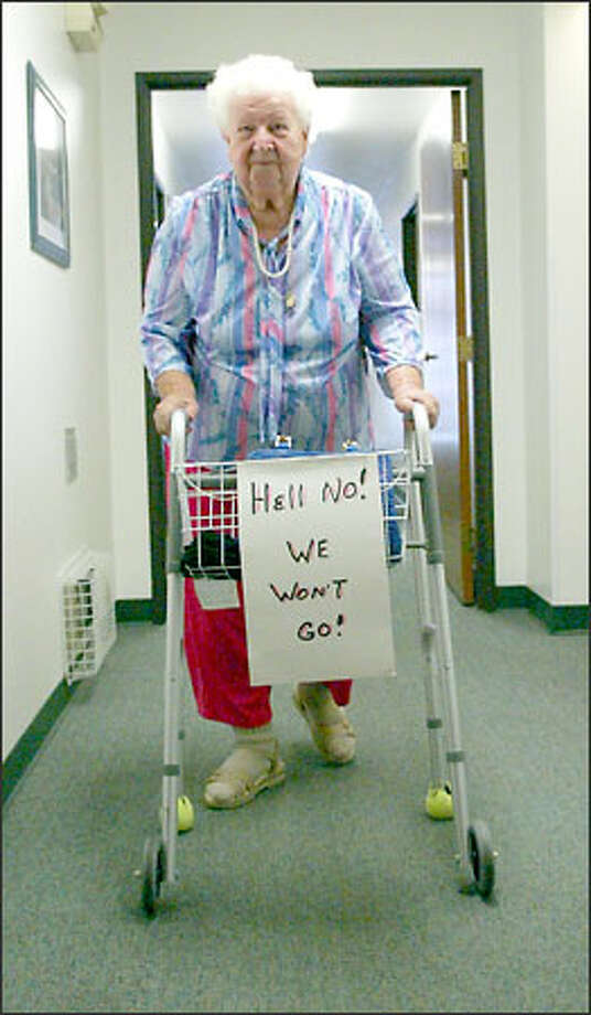 Beatrice Weber makes her way to her room sporting a sign showing her feelings about being evicted from Alderwood Assisted Living in Lynnwood by the state Department of Social and Health Services. Photo: David Bitton/Seattle Post-Intelligencer