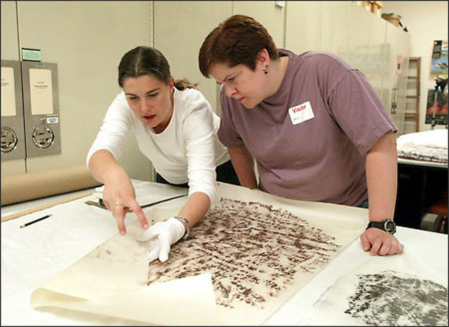 "Kelly Meyers, left, and Ann Gillespie examine a Native American ""rubbing"" at the Burke Museum. The rubbing was taken from a petroglyph in 1953. Photo: David Bitton/Seattle Post-Intelligencer"
