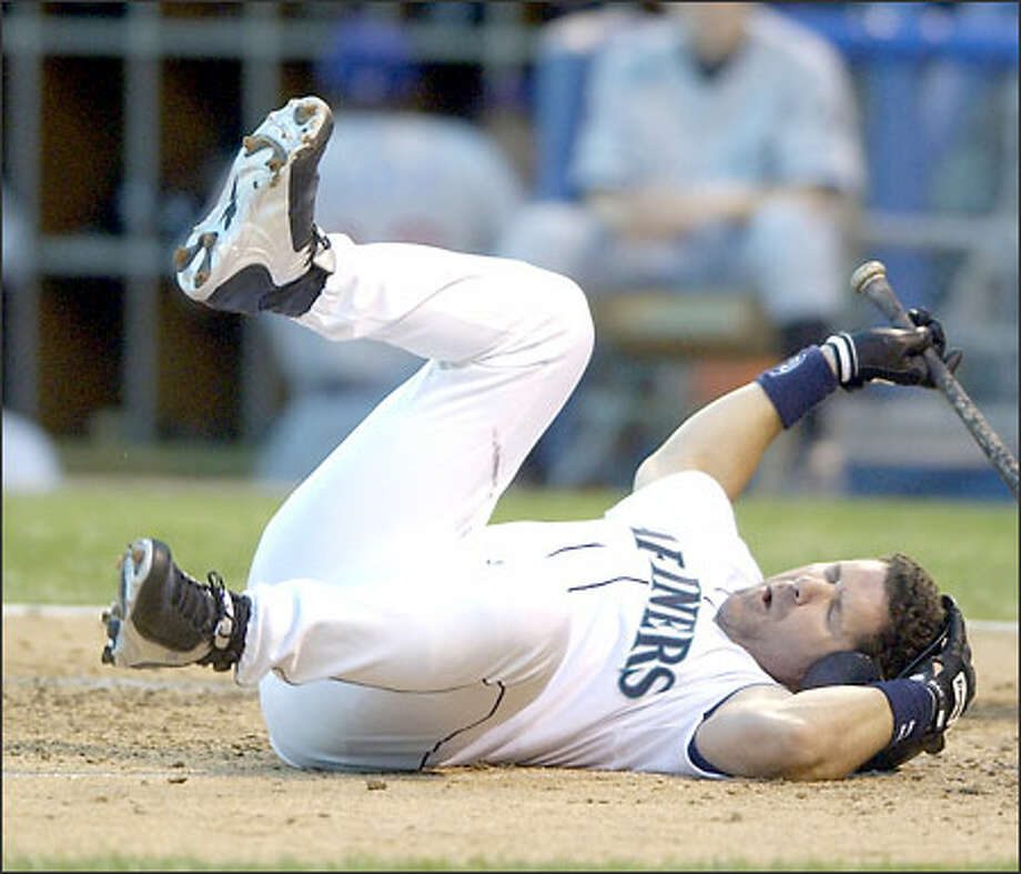 Edgar Martinez hits the ground after he was beaned by Jason Schmidt's fastball in the first inning. Martinez, whose helmet was cracked, stayed in the game. Photo: MARK DUNCAN/AP