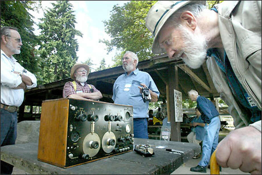 Carle Graffunder checks out an IP 501, a longwave radio telegraph used in the 1920s and '30s, at a reunion in Woodland Park yesterday of the radio operators and linemen of the Alaska Communications System. From left to right in the back of the table are Jim Tipple, Dan Hagedoran and Bob Watson. Photo: Karen Ducey/Seattle Post-Intelligencer