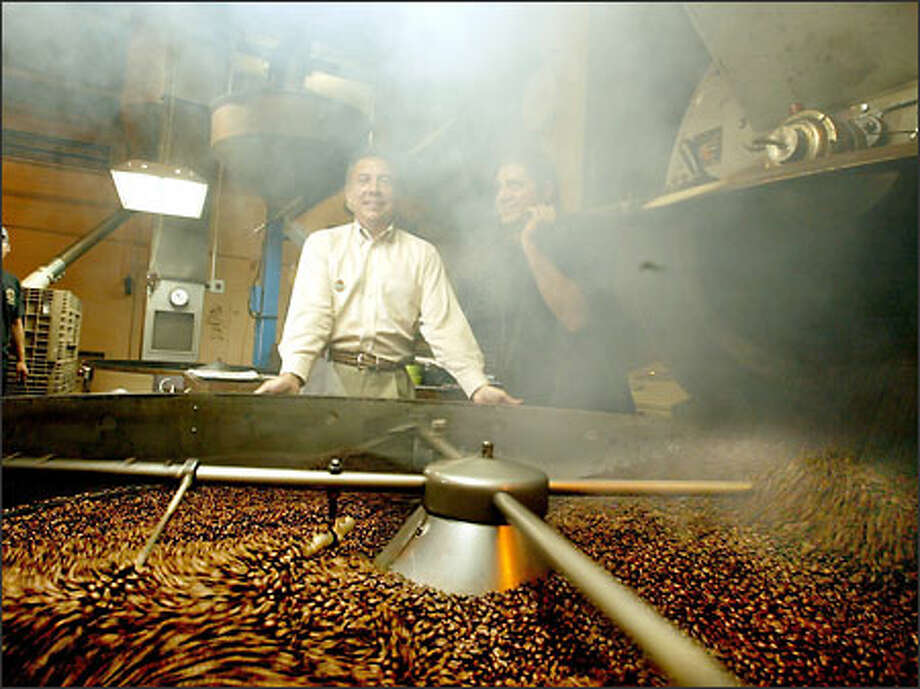 Tony Gioia, president and chief executive at Tully's Coffee Corp., is partially obscured by the steam as he takes in the smell of roasted coffee beans yesterday at the plant in Seattle. The company has introduced coupon books and expanded the availability of ice cream to more stores. Photo: Scott Eklund/Seattle Post-Intelligencer