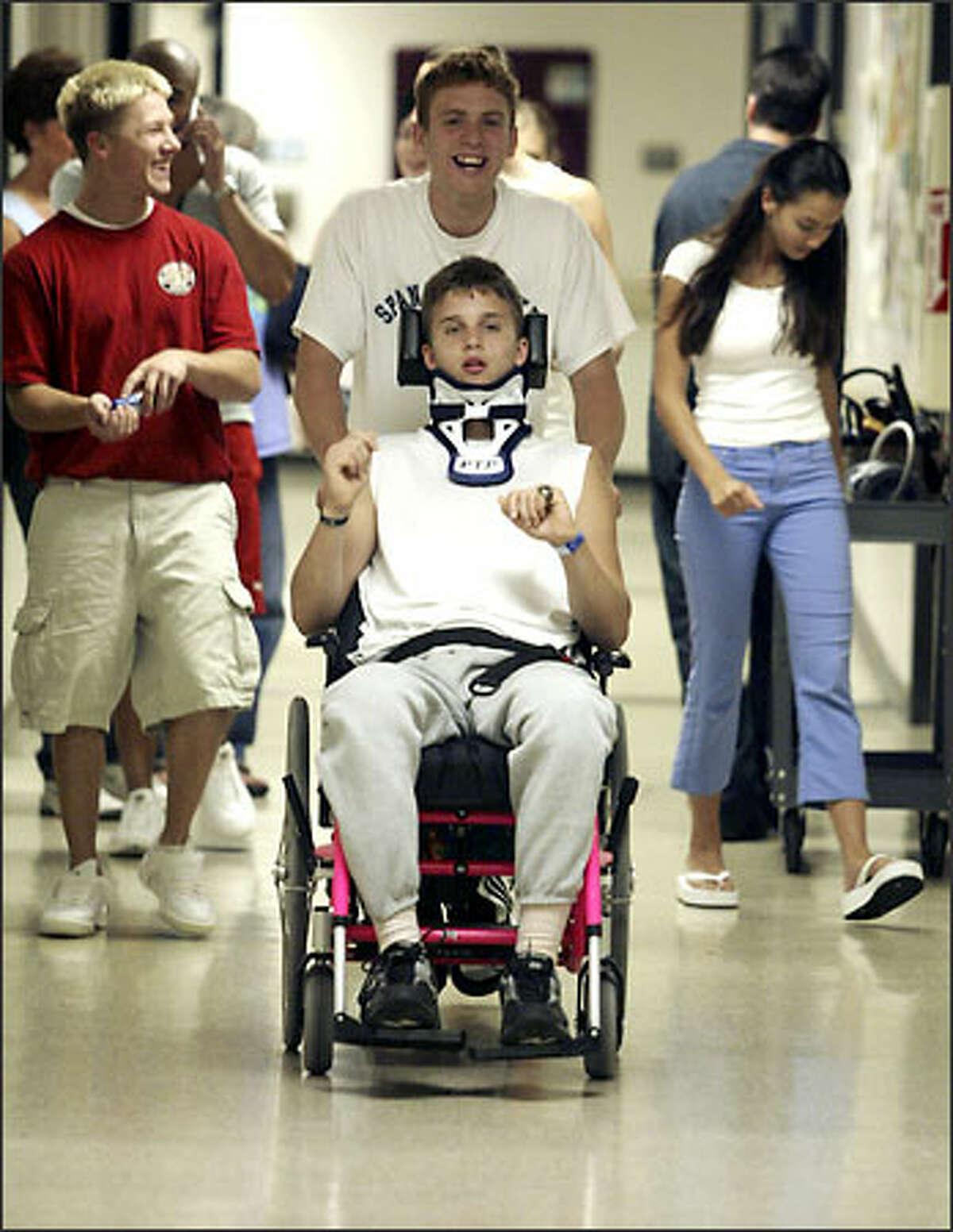 Spanaway Lakes teammate Steven Easterly gives Logan Seelye a push back to his room at Good Samaritan Hospital after rehab treatments.