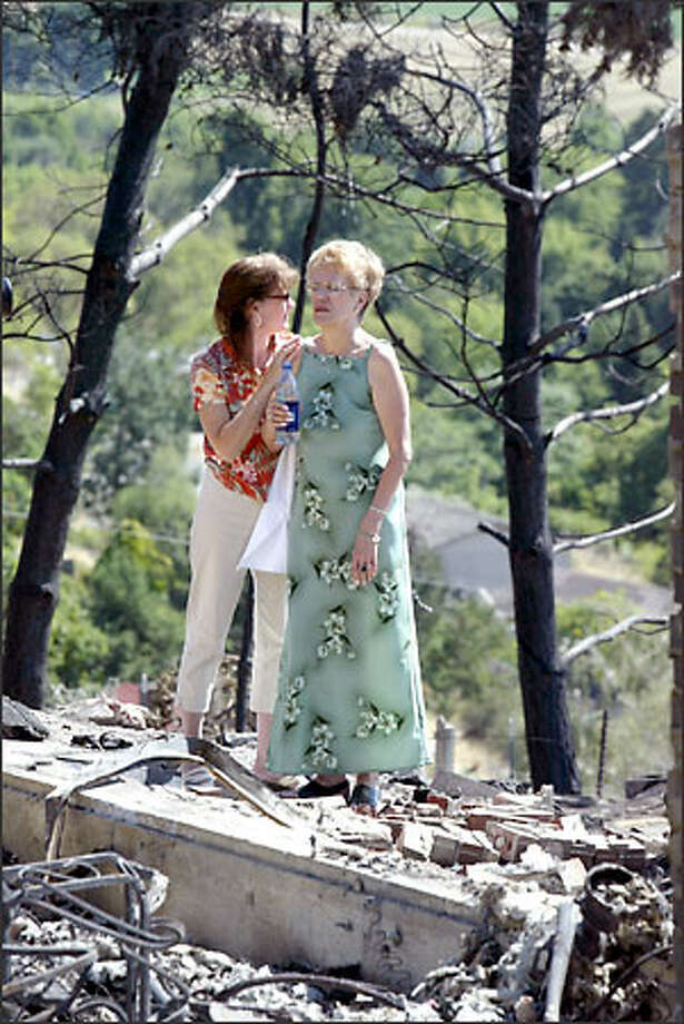 Lynette Grandy, left, comforts Jackie Bradley, whose home in Okanogan was one of five destroyed this week by a fast-moving blaze. Bradley recently lost her husband of 35 years to a heart attack. Photo: Karen Ducey/Seattle Post-Intelligencer