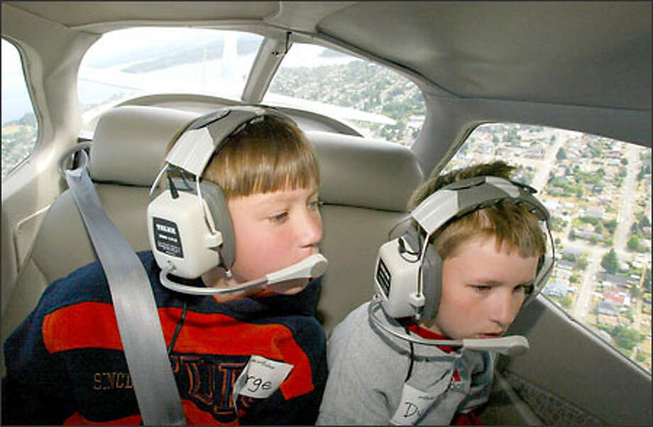 George Kamerzan, left, and Dylan Mullen, both 11, get a bird's-eye view of Seattle from the window of a Cessna during an aviation camp this week. Photo: David Bitton/Seattle Post-Intelligencer