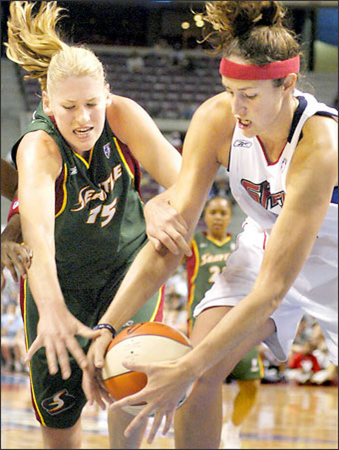 Storm forward Lauren Jackson grabs Detroit center Ruth Riley as they pursue a loose ball during the second half of the Shock's 74-61 victory Friday night at Auburn Hills, Mich. Jackson led all scorers with 23 points. Teammate Sue Bird, bothered by a sore left knee, added 14 points. Bird played just eight minutes during the second half. With Bird on the bench, Detroit outscored Seattle 14-5 in the final four minutes of the game. Photo: / Associated Press
