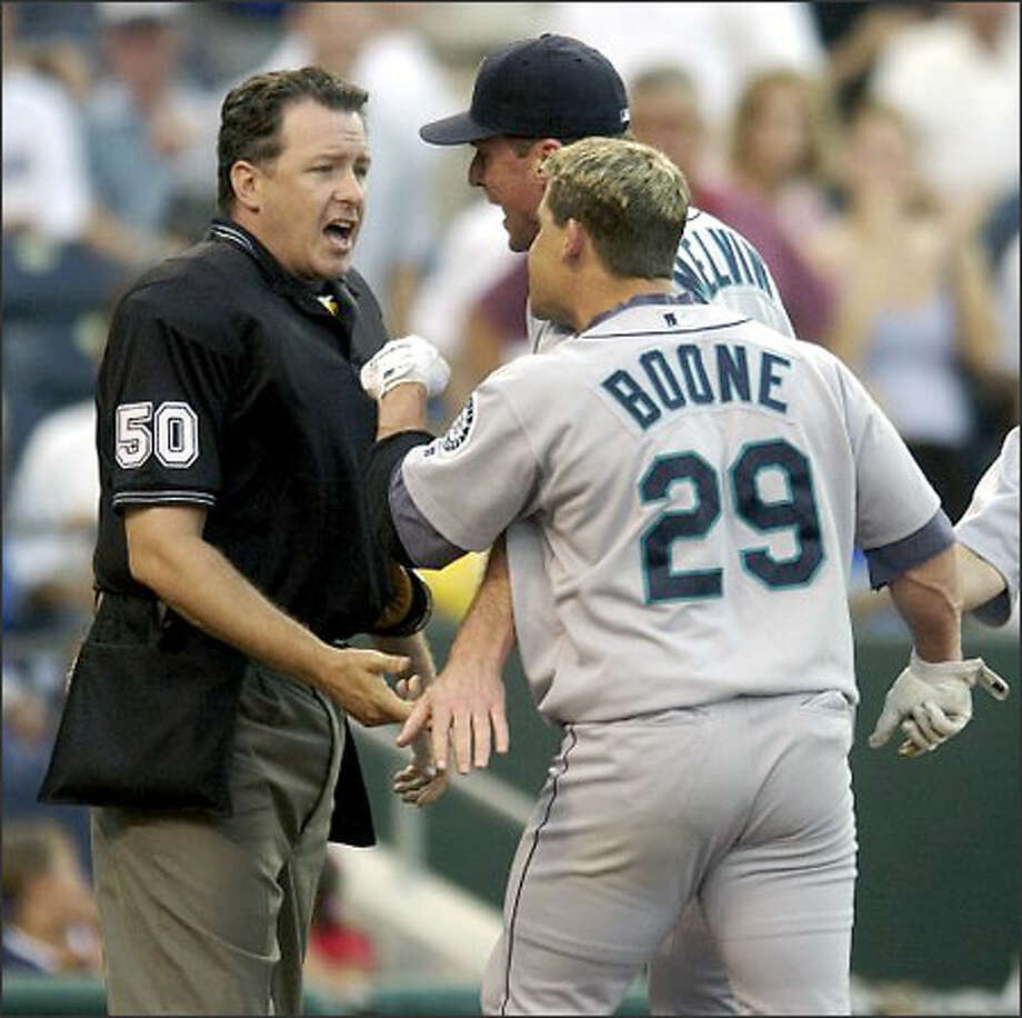 Mariners second baseman Bret Boone (29) and manager Bob Melvin argue with umpire Paul Emmel after Boone was ejected in the first inning against the Kansas City Royals. Boone, who struck out to end the inning, was ejected after he threw his bat and helmet while leaving the plate. Photo: / Associated Press