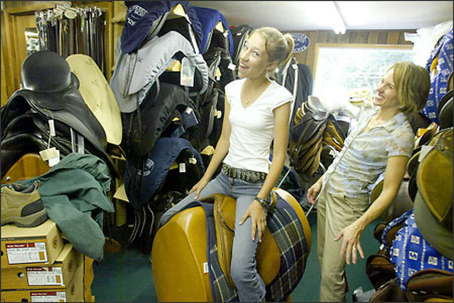 Gabrielle Hansen, left, clowns around with manager Heather Manuel as she tries out a used saddle at Olson's Tack Shop in Bellevue. The business, now catering to English riders, opened in 1945. Photo: Jim Bryant/Seattle Post-Intelligencer