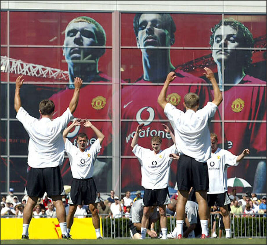 Manchester United players warm up at Sunday's practice beneath an image of teammates at the Nike World Headquarters in Beaverton, Ore. Photo: / Associated Press