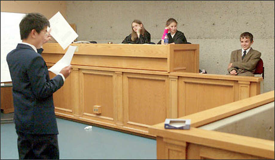 Jesse Teng, 12, left, questions Kelvin Bates, 13, right, during a mock trial. The judges were Naomi Lewy, 13, left center, and Vanessa Steinberg, 12. Photo: David Bitton/Seattle Post-Intelligencer
