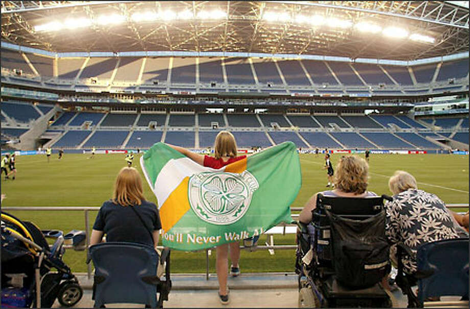 Soccer fan Sarah Adams of Spokane sports a Celtic flag, watching the Scottish team work out at Seahawks Stadium in preparation for tonight's match with its British archrival. Photo: Mike Urban/Seattle Post-Intelligencer