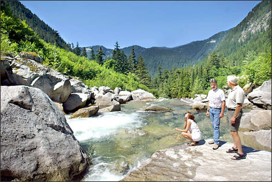 "From left to right: Dawna Finley, Mike Finley and Ed Husmann, all from Index,WA,  visit a recreational area on the north fork of the Skykomish River in the Mt. Baker Snoqualmie National Forest  which people will no longer be able to access if the proposed Wild Sky Wilderness Area designation passes.  Their group, Forests for People, is fighting this proposal because the wilderness designation will tear out or close roads and bridges people currently use to access remote areas.  ""This is a place where you can go and find nobody...... even on weekends."" says Mike Finley.  The Finley's own and operate A River's Edge Country Cottage Bed and Breakfast out of Index,WA. Photo: Karen Ducey/Seattle Post-Intelligencer"