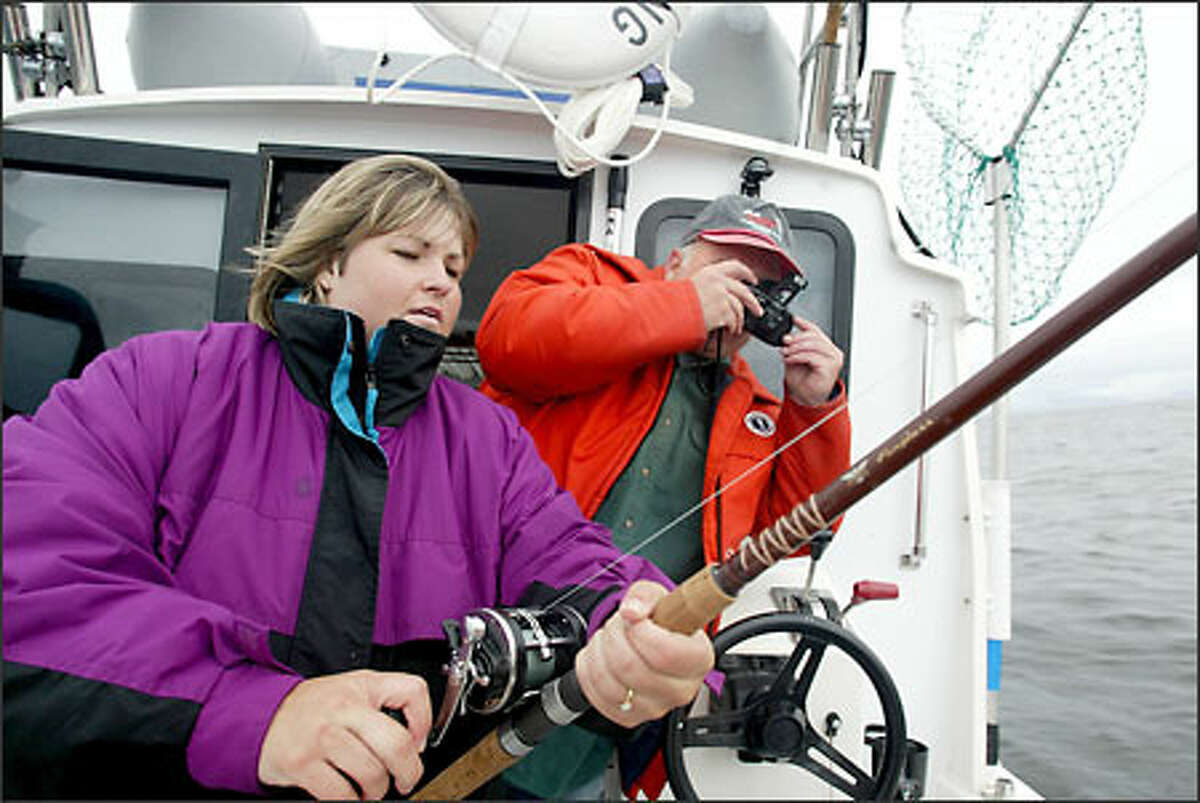 Kim Clark of the Tri-Cities reels in a salmon aboard the charter vessel Shelbie Tessa as her boyfriend Dave Bushey, also of the Tri-Cities, immortalizes the moment about six miles west of La Push.