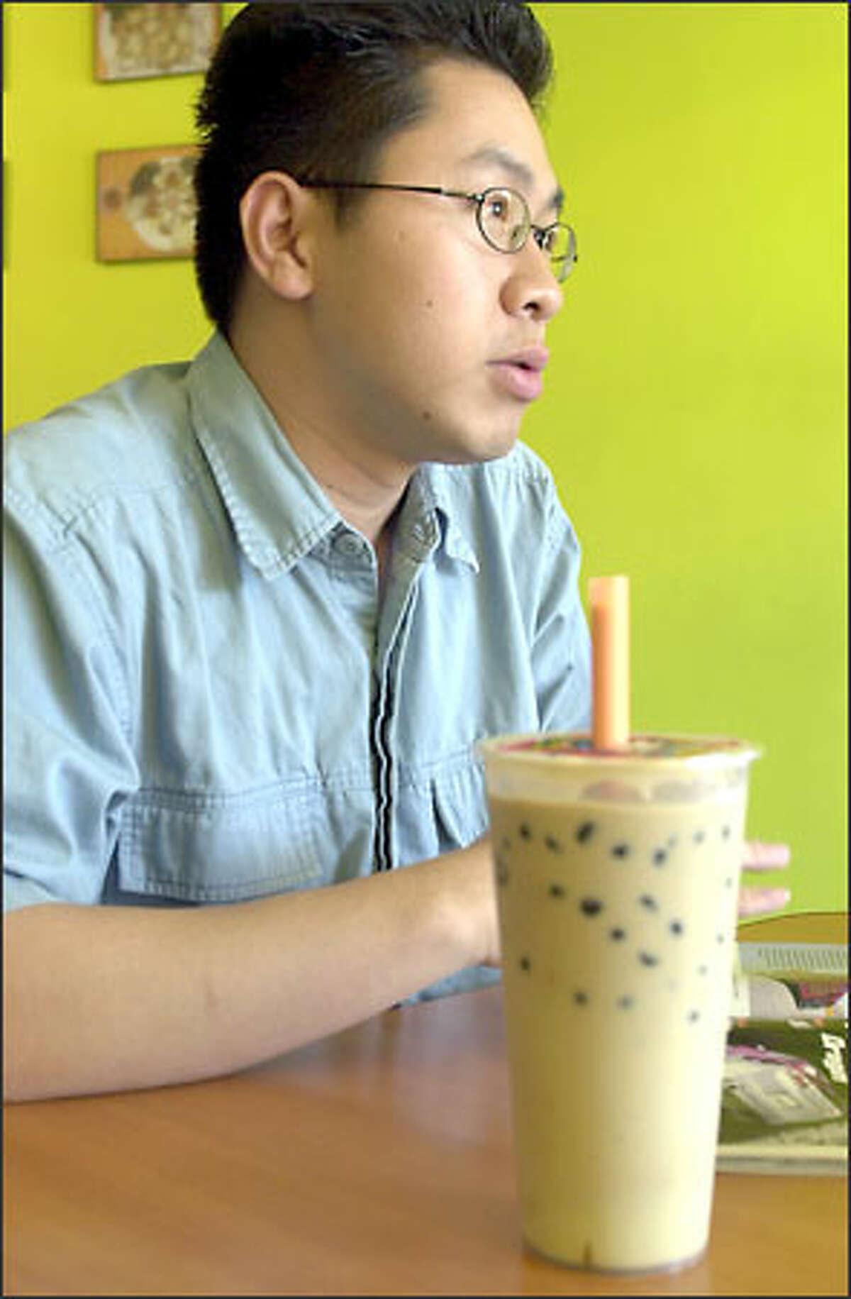 Hendy Hartono of Seattle takes a break with his favorite bubble tea flavor, avocado, at the Pochi Tea Station in the U District.