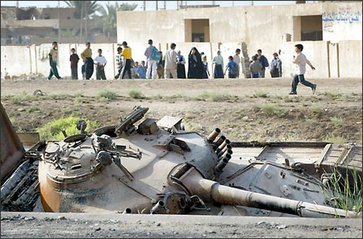 A war-damaged Iraqi tank rests along the highway next to a school on the outskirts of Baghdad. Depleted uranium weapons were used in populated areas in Iraq.
