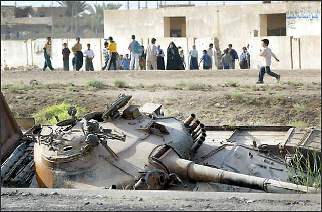 A war-damaged Iraqi tank rests along the highway next to a school on the outskirts of Baghdad. Depleted uranium weapons were used in populated areas in Iraq. Photo: Dan DeLong/Seattle Post-Intelligencer