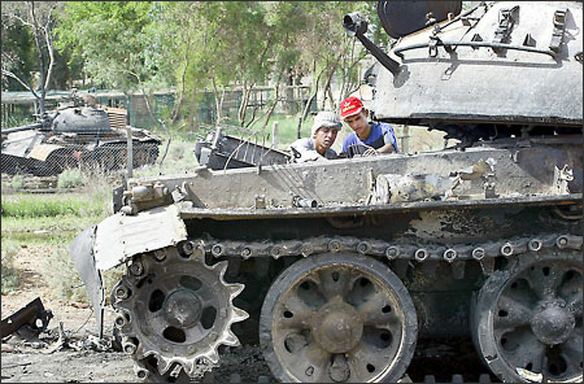Outside Kut in southern Iraq, two young Iraqi men remove parts from one of the many tanks in the area.