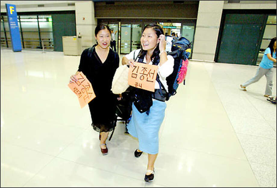 Lindsay and Courtnay Peifer, right, arrive at Inchon International Airport, holding signs that bear their Korean names, nearly 25 years after they left. Photo: Meryl Schenker/Seattle Post-Intelligencer