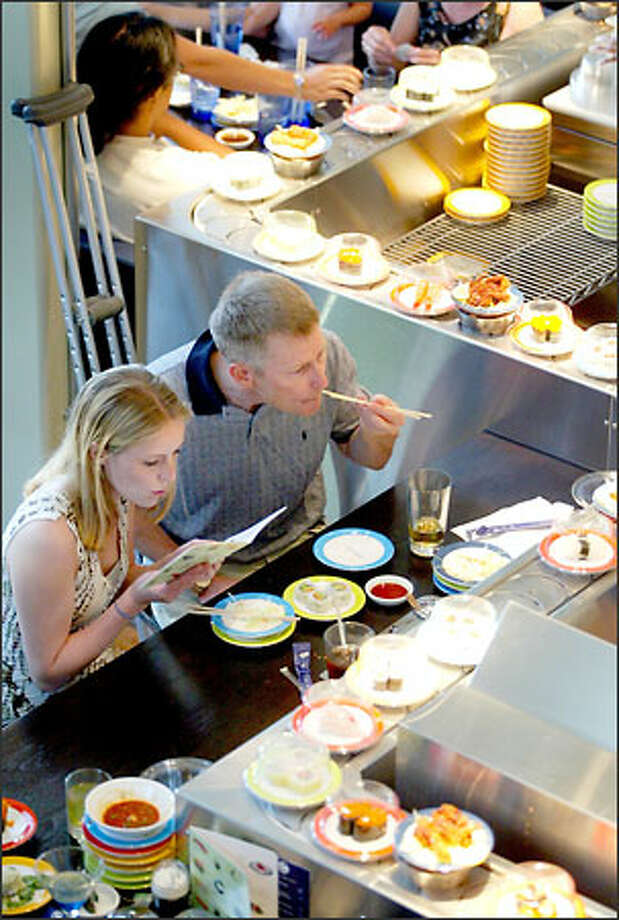 "Carin Berg tries to figure out what she is eating while her father, Stephen Berg, just eats it. ""I have no idea what it is, but it is good!"" he said. Sushi is served Kaiten style, or on a conveyer belt, at the Blue C Sushi restaurant, which opens today in Fremont. Photo: Mike Urban/Seattle Post-Intelligencer"