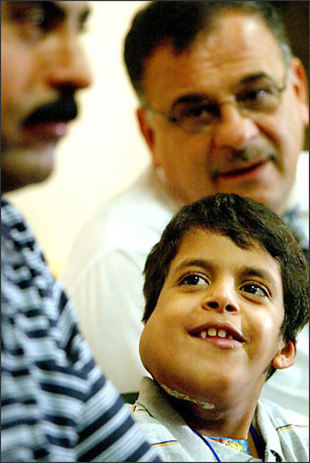 Ali Mousa Souad, 8, listens to Walid Farhoud's translation of a reporter's question for him and waits for his father, Mousa Souad, at left to answer for him.