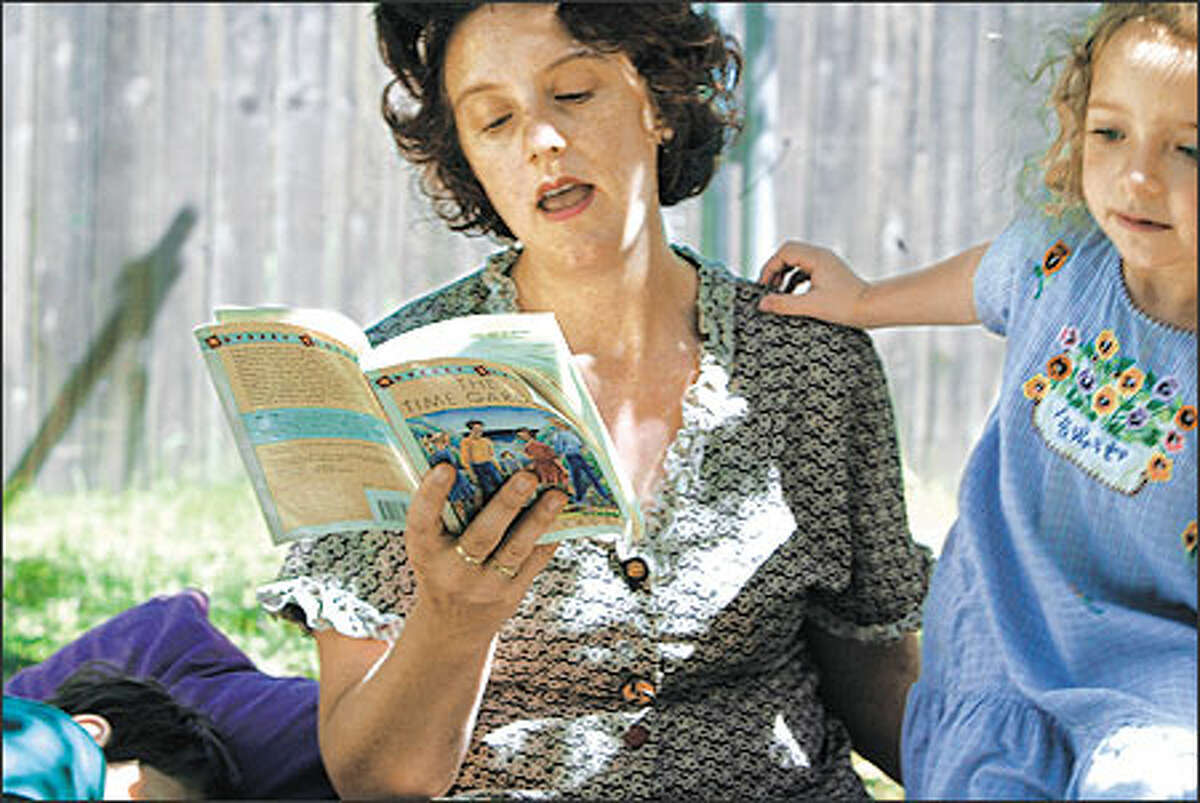 """Five-year-old Lillie Brown, right, responds as her mother, Paula Becker, reads aloud from the novel """"The Time Garden"""" by Edward Eager. Restored classics bring back times that seem friendly and secure to today's children and parents."""