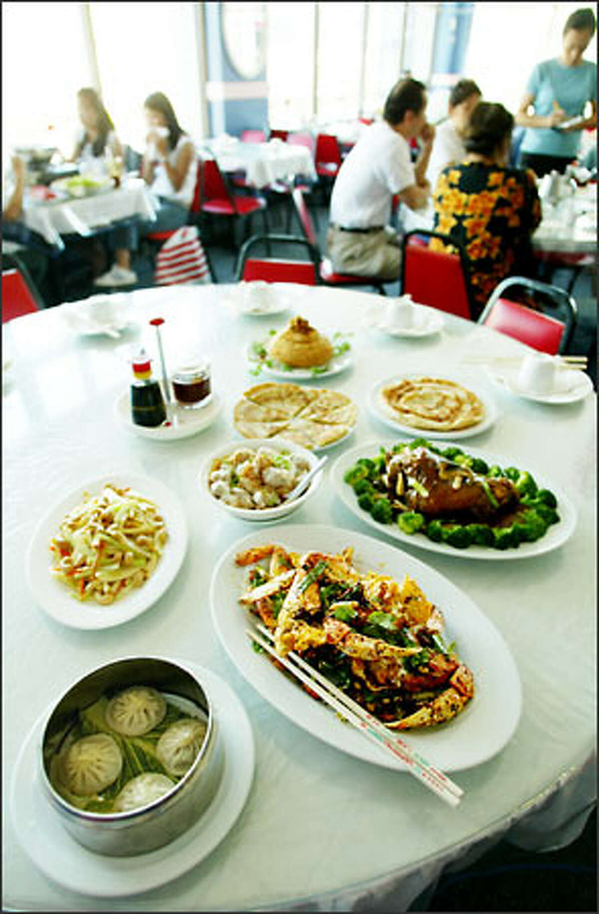 Some of the specialties of Seven Stars Pepper Szechuan Restaurant include, at left foreground, steamed pork buns and Szechuan crab.