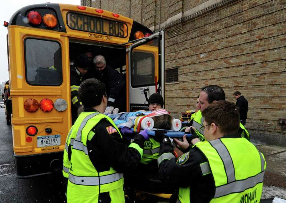 Albany Fire Department and Mohawk Ambulance EMS workers remove an injured child from a Schodack Central School District Bus on North Pearl Street in Albany, New York March 14, 2011 after an accident that occurred on the way to a performance of Aesop's Fables at the Palace Theatre..    (Skip Dickstein / Times Union) Photo: SKIP DICKSTEIN
