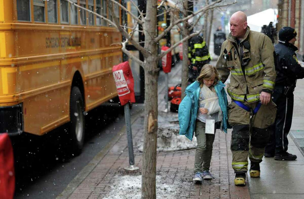 Ken Sober, of the Albany Fire Department, stands with his daughter, Julia, one of the students who was injured in the Monday bus accident. Sober was stationed elsewhere in the city, but was alerted by colleagues his daughter was on one of the Schodack Central School District buses that collided on the way to a performance of ?Aesop?s Fables?? at the Palace Theatre. Julia was treated and released at Albany Medical Center Hospital for what appeared to be bruises, according to her mother, Jennifer Sober.
