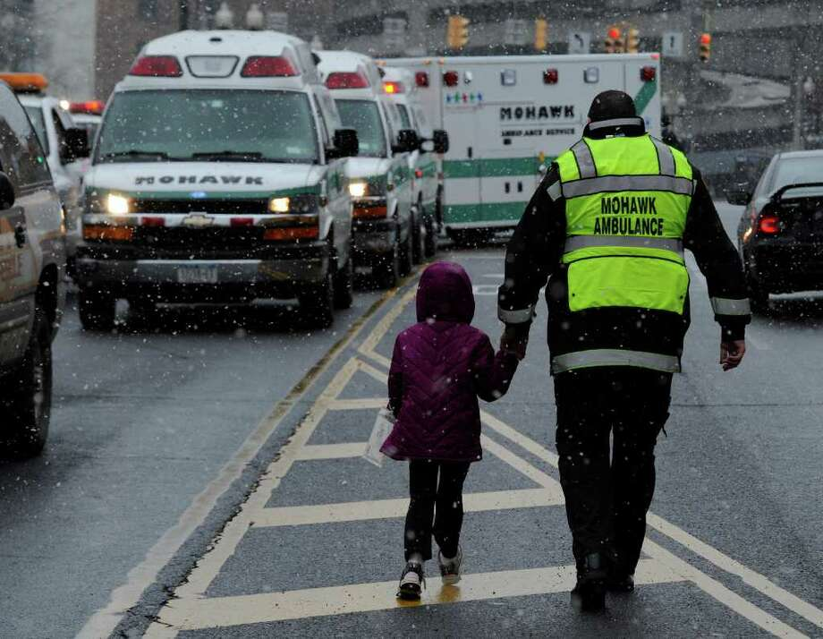 A Mohawk Ambulance EMS member assists an injured child Monday from a Schodack Central School District bus on North Pearl Street in Albany. (Skip Dickstein / Times Union) Photo: SKIP DICKSTEIN