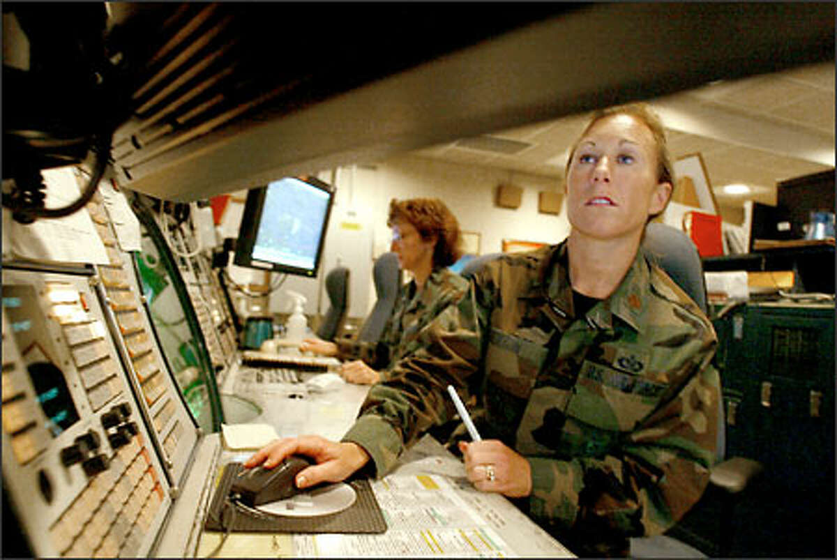 Air Force Maj. Kari Sexton watches a monitor in the Western Air Defense Sector Headquarters at McChord Air Force Base. Sexton was performing the same duty on Sept. 11, 2001.