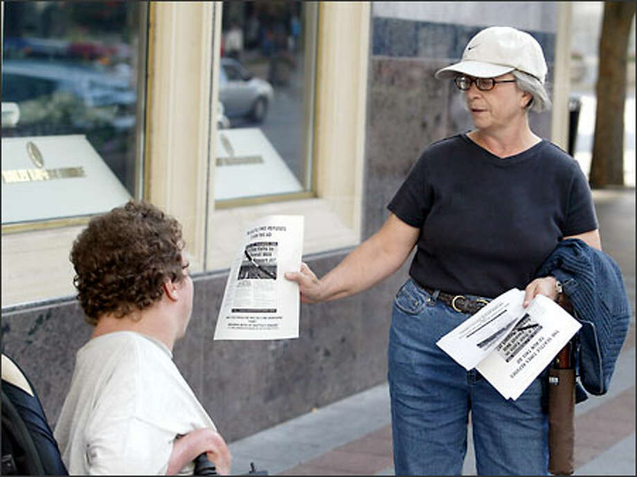 Edith Keenan of Seattle, a supporter for the Committee for a Two-Newspaper Town, hands out a copy of an ad that The Seattle Times has refused to run, to Rodney Lewis, also of Seattle, near Westlake Center. Photo: Scott Eklund/Seattle Post-Intelligencer