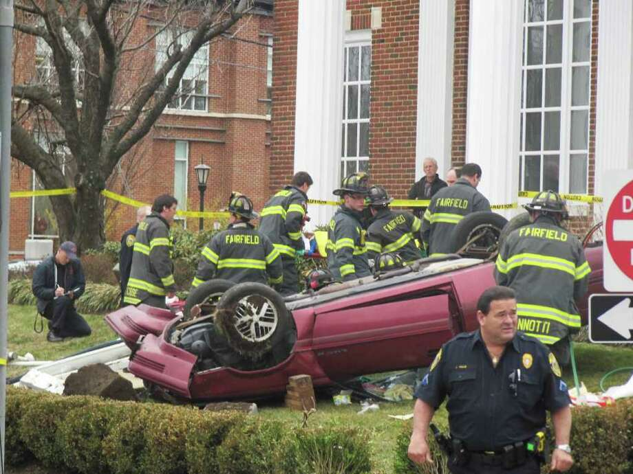 Firefighters attend to an elderly woman around noon on Monday after her car rolled over onto the Chase Bank property at Post Road and Unquowa Road. She had to be extricated from her vehicle. Photo: Kirk Lang / Fairfield Citizen