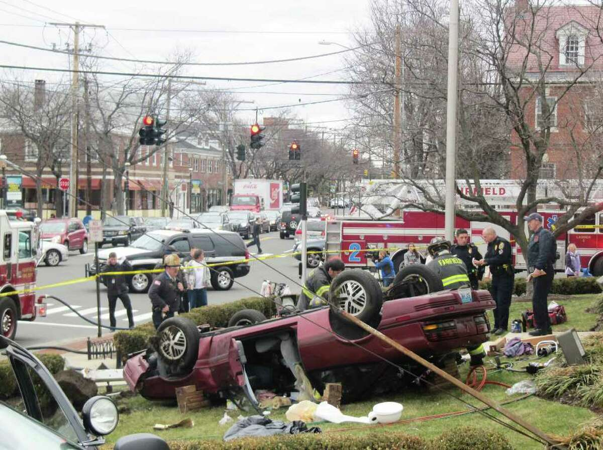 Firefighters attend to an elderly woman around noon on Monday after her car rolled over onto the Chase Bank property at Post Road and Unquowa Road. She had to be extricated from her vehicle.