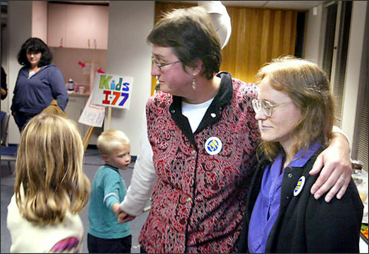 Dorothy Gibson, center, a supporter of the espresso tax measure, is consoled by her children, Simon Gibson-Penrose and Isabel Gibson-Penrose, and hugs fellow supporter Betty Williams as early returns show voters rejecting Initiative 77.