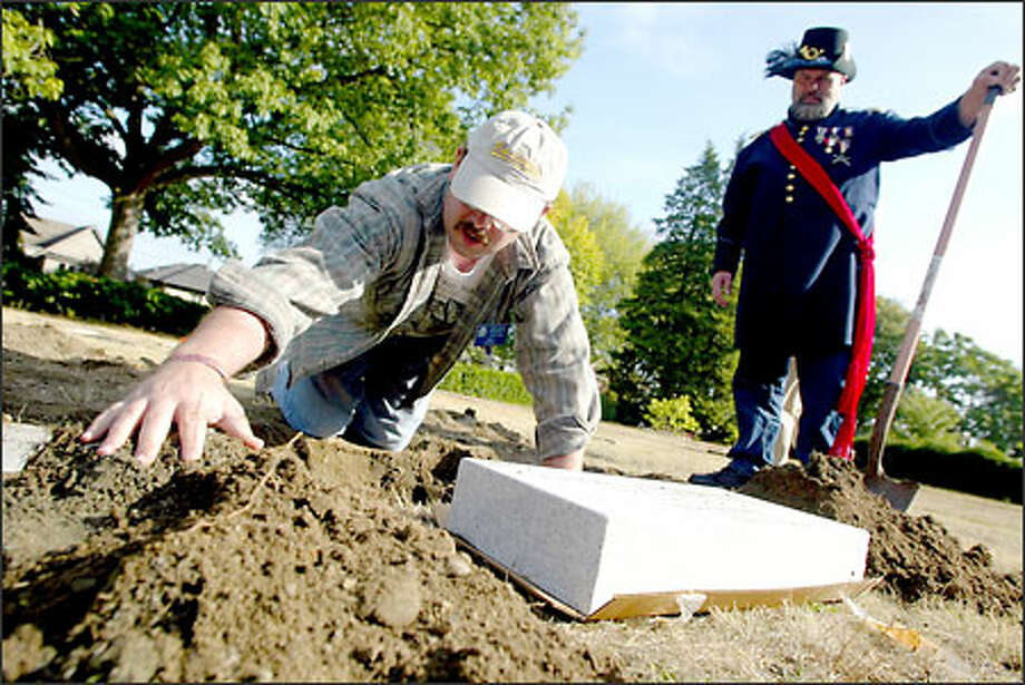 Ken Richmond of the Sons of Union Veterans of the Civil War watches as Rod Fleck replaces a headstone at a cemetery for Civil War vets on Capitol Hill. Photo: Joshua Trujillo/Seattle Post-Intelligencer