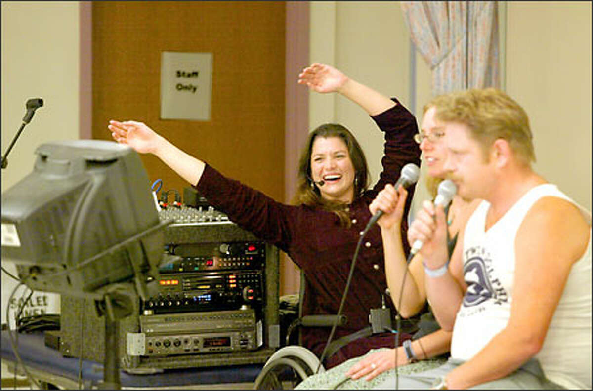 Christine Duggan gets into the mood of the song as patient Eric Anderson, right, and recreational therapist Chrystal Smith hook up for a duet during karaoke at Harborview Medical Center.