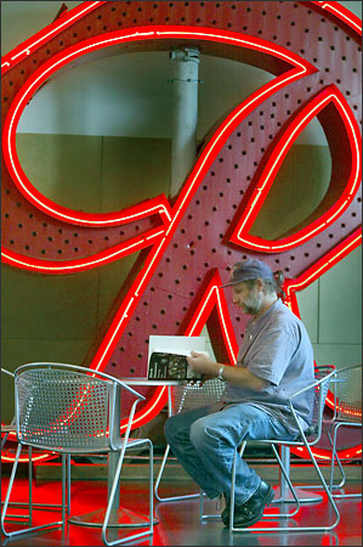 The old Rainier Brewing sign lights up the gift shop of the Museum of History and Industry -- and Phil Ackerman. The museum is trying to preserve Seattle's old neon signs, though it's competing for them with collectors.